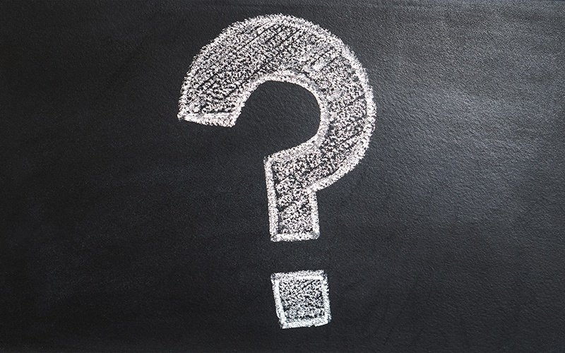 A large question mark in chalk on a blackboard